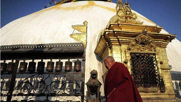 Буддийский монах у молельных колес и Ступы. Архивное фото.