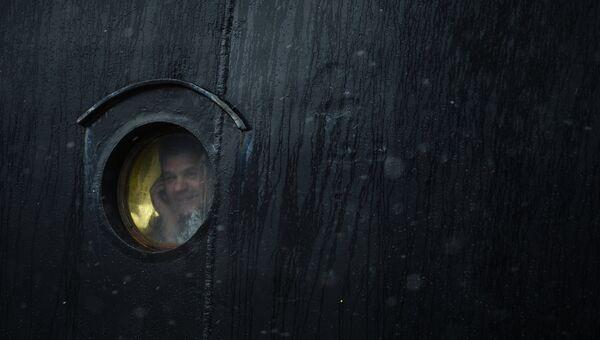 Мужчина в иллюминаторе атомного ледокола 50 лет Победы перед отплытием ледокола с Олимпийским огнем на Северный полюс.