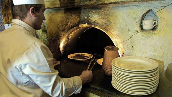 Повар готовит национальное блюдо в печи. Архивное фото