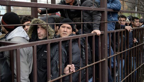 Граждане иностранных государств стоят в очереди в центральное отделение УФМС РФ по Москве. Архивное фото