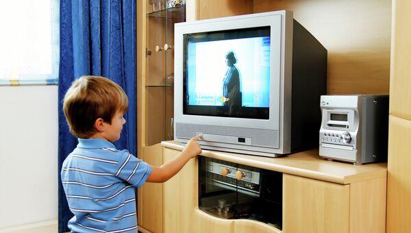 Ребенок смотрит телевизор, архивное фото