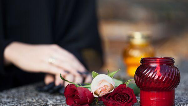 Цветы и свечи на могильном камне, архивное фото