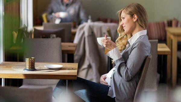Беременная женщина с кофе. Архивное фото
