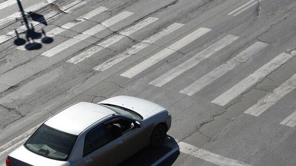 Автомобиль стоит у стоп-линии перед пешеходным переходом