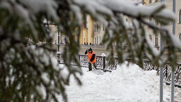 Дворник убирает улицу Томска после сильного декабрьского снегопада