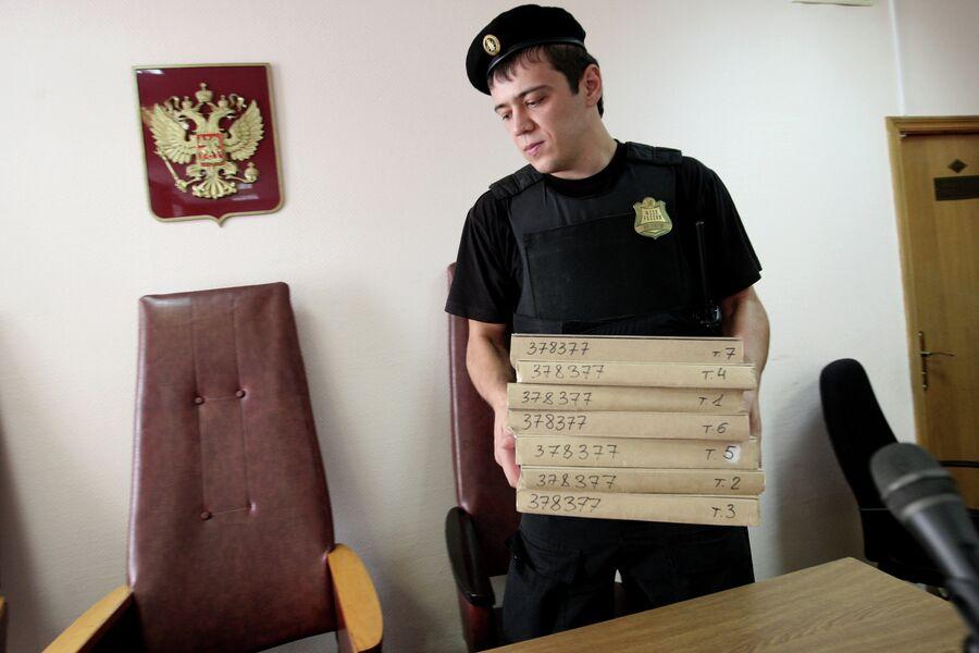 Судебный пристав держит в руках папки с документами