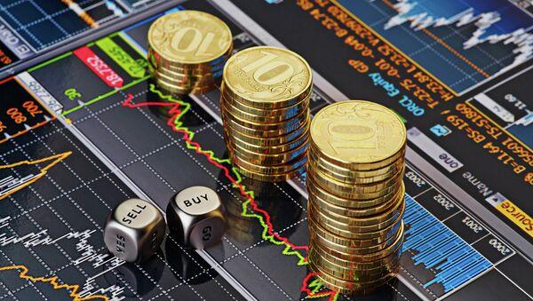 Стопки десятирублевых монет на экране с биржевыми графиками. Архивное фото