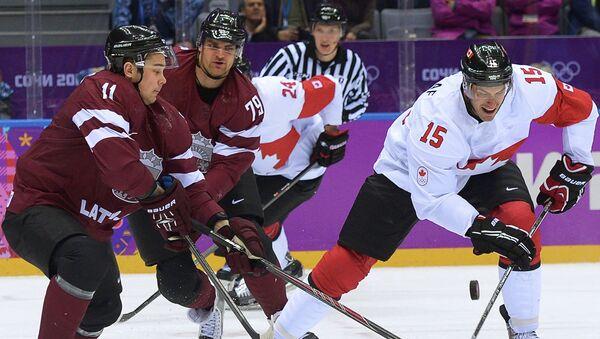 Латвийский хоккеист Виталий Павлов (второй слева) в матче против команды Канады на Играх в Сочи