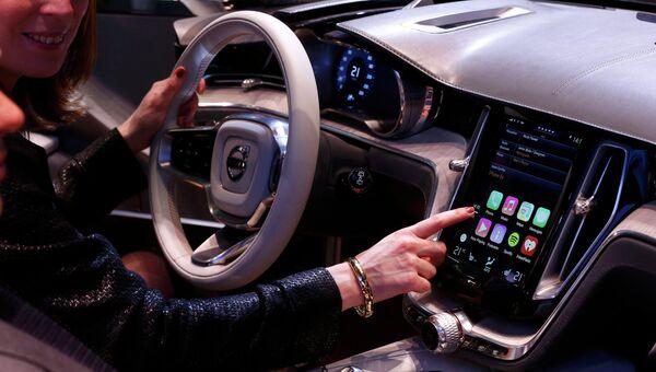 Женщина демонстрирует дисплей с функцией CarPlay на автосалоне в Женеве. Фото с места события