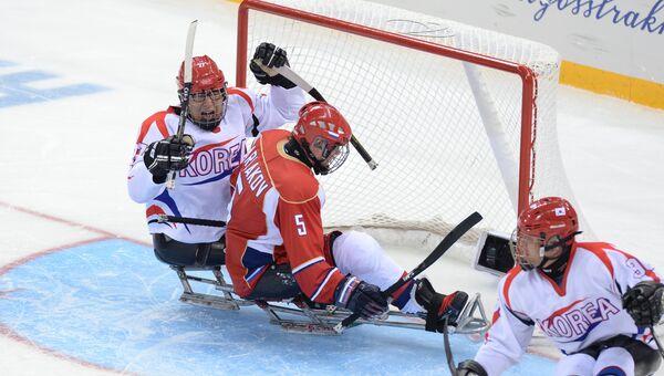 Слева: Бунг-Сок Чо (Южная Корея) радуется забитому голу в матче отборочного этапа между сборными командами России и Южной Кореи в соревнованиях по следж-хоккею на XI зимних Паралимпийских играх в Сочи.