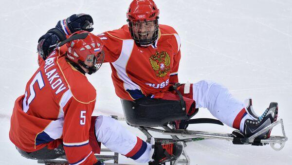 Василий Варлаков и Евгений Петров (Россия) радуются забитому голу в матче отборочного этапа между сборными командами России и Италии в соревнованиях по следж-хоккею на XI зимних Паралимпийских играх в Сочи.