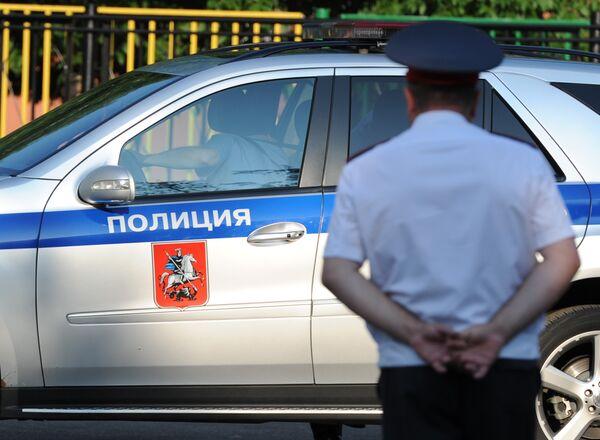 Полицейский автомобиль и сотрудник полиции.