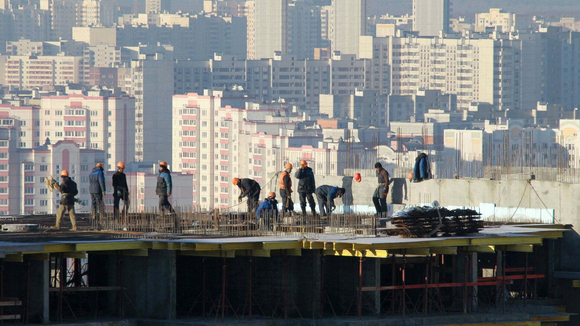 Рабочие на строительстве одного из корпусов жилого комплекса - РИА Новости, 1920, 27.08.2020