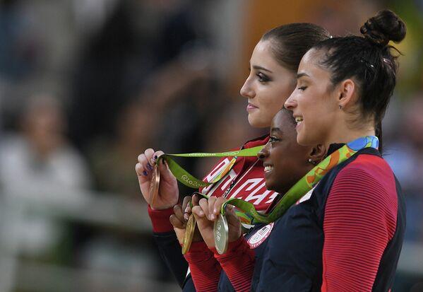 Алия Мустафина, Симона Байлз и Александра Райсман (слева направо)
