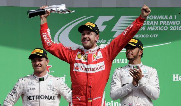 Пилот Феррари Себастьян Феттель (в центре), занявший третье место на Гран-при Мексики
