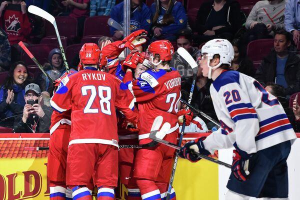 Хоккеисты молодежной сборной России по хоккею (слева) радуются заброшенной шайбе
