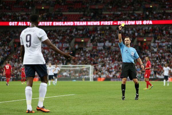 Арбитр Иван Кружльяк показывает желтую карточку нападающему сборной Англии Данни Уэлбеку
