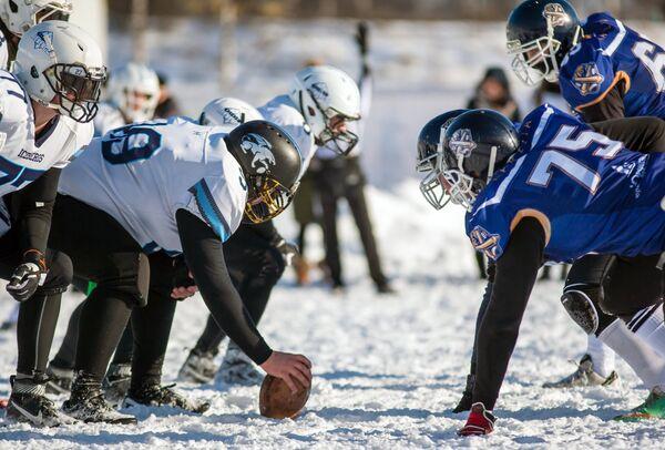 Игроки команды Айсберги (слева) и игроки команды Оружейники в матче ежегодного турнира северных городов Snow Bowl 2017 по американскому футболу