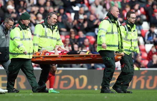 Медицинские работники уносят на носилках с поля футболиста Сандерленда Билли Джонса