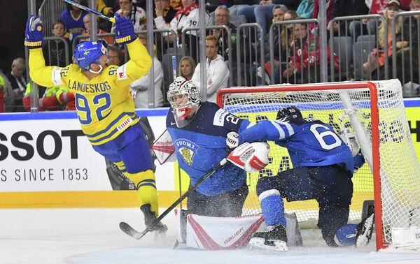 Форвард сборной Швеции Габриэль Ландеског (слева) и вратарь сборной Финляндии Харри Сятери (в центре)