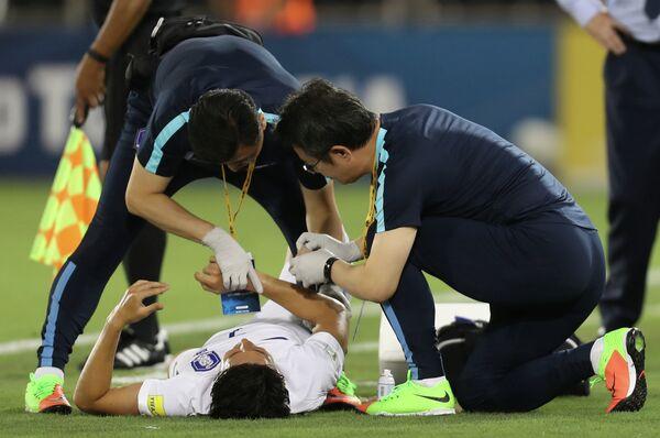 Медики оказывают помощь форварду сборной Кореи Сон Хын Мину