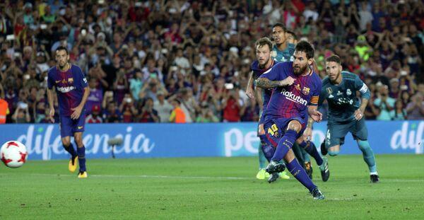 Форвард Барселоны Лионель Месси забивает мяч в ворота Реала