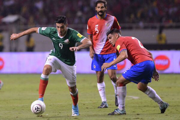Нападающий сборной Мексики Рауль Хименес (слева) и защитник сборной Коста Рики Джонни Акоста (справа)