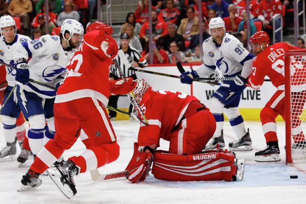 Нападающий Тампы Бэй Лайтнинг Никита Кучеров (слева) забрасывает шайбу в ворота Детройт Ред Уингз