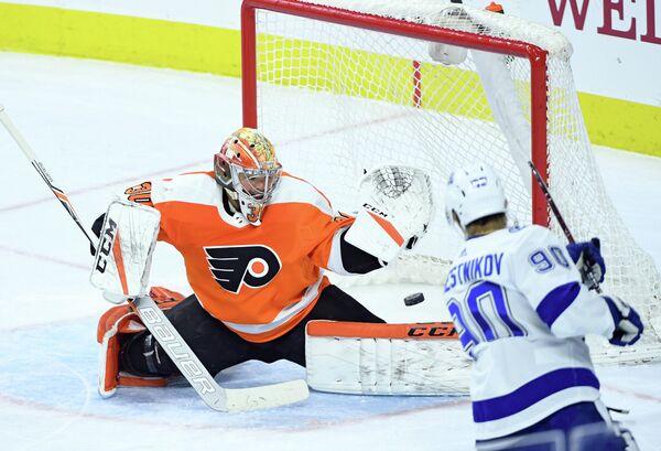 Нападающий клуба НХЛ Тампа Бэй Лайтнинг Владислав Наместников (справа) забрасывает шайбу в ворота вратаря Филадельфии Флайерз Михала Нойвирта