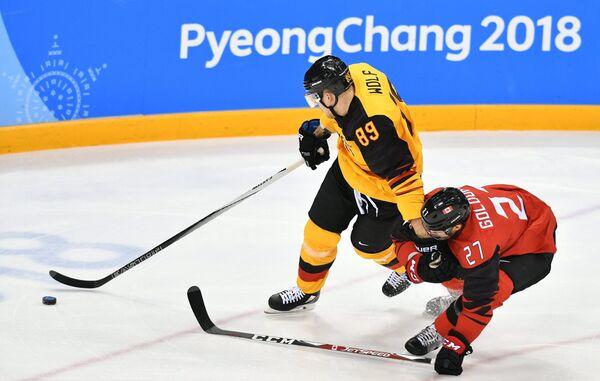 Немецкий хоккеист Давид Вольф и хоккеист сборной Канады Коди Голаубеф (слева направо)