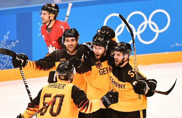 Хоккеисты сборной Германии Патрик Хагер, Дэрил Бойл, Маттиас Плахта, Феликс Шютц (слева направо) радуются заброшенной шайбе
