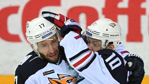 Хоккеисты Металлурга Войтек Вольский (слева) и Сергей Мозякин радуются заброшенной шайбе