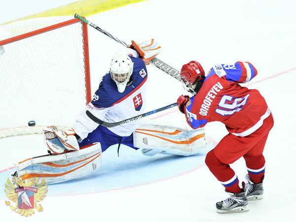 Форвард юниорской сборной России (до 18 лет) Павел Дорофеев (справа) забрасывает буллит