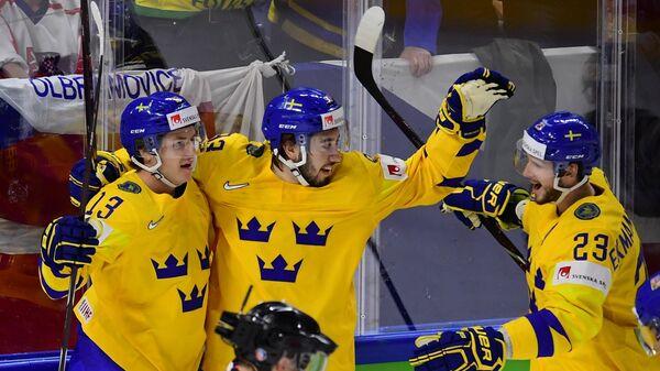 Хоккеисты сборной Швеции Маттиас Янмарк, Мика Зибанеджад и Оливер Экман-Ларссон (слева направо) радуются заброшенной шайбе