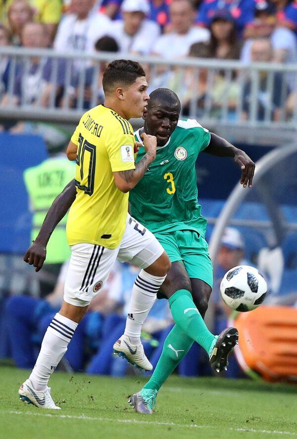 Полузащитник сборной Колумбии Хамес Родригес и защитник сборной Сенегала Калиду Кулибали (слева направо)