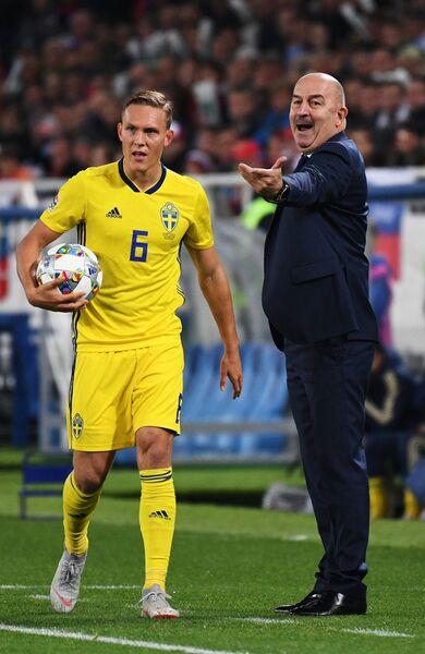 Защитник сборной Швеции Людвиг Аугустинсон и главный тренер сборной России Станислав Черчесов (справа)