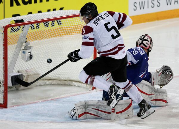 Нападающий сборной Латвии Янис Спруктс забрасывает шайбу в ворота голкипера Франции Кристобаля Юэ