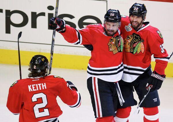Нападающий Чикаго Патрик Шарп с партнерами по команде Михалом Розсивалом и Данканом Кейтом радуется заброшенной шайбе в ворота Бостона во второй игре финальной серии НХЛ