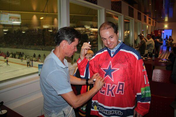 Вячеслав Быков (слева) подписывает футболку болельщику