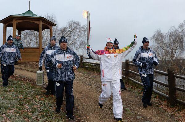 Факелоносец во время эстафеты олимпийского огня в городе Плес Ивановской области