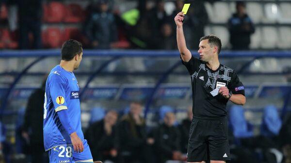 Гедиминас Мажейка (справа) показывает желтую карточку игроку ФК Тромсе Хендрику Хельмке (слева)