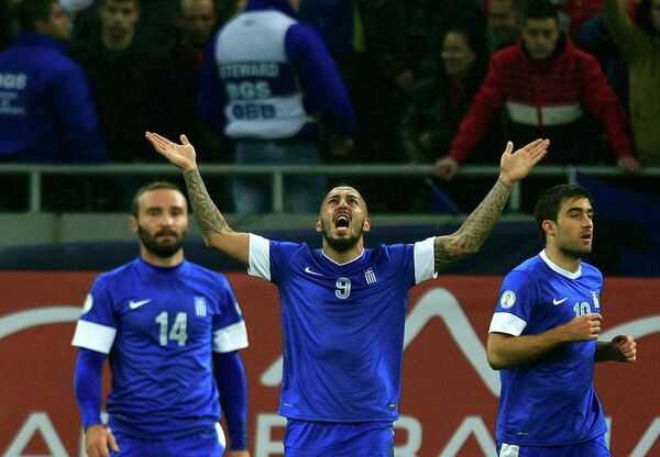 Нападающий сборной Греции Костас Митроглу радуется забитому мячу в ворота румын