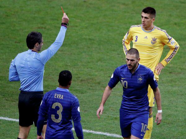 Арбитр Дамир Скомина показывает красную карточку защитнику сборной Украины Евгению Хачериди