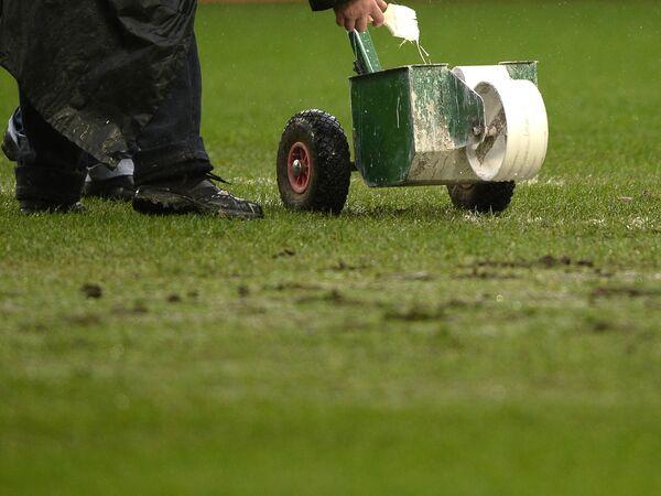 Работник стадиона делает разметку поля