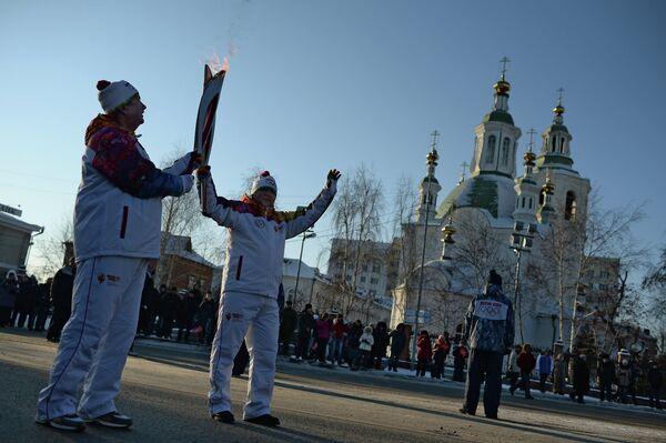 Факелоносцы во время передачи эстафеты олимпийского огня в Тюмени
