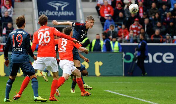 Полузащитник Баварии Бастиан Швайнтайгер (крайний справа) забивает мяч в ворота Майнца