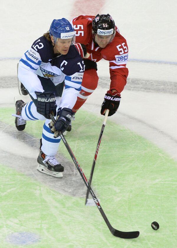Форвард сборной Финляндии Олли Йокинен (слева) и защитниксборной Канады Марк Шайфли