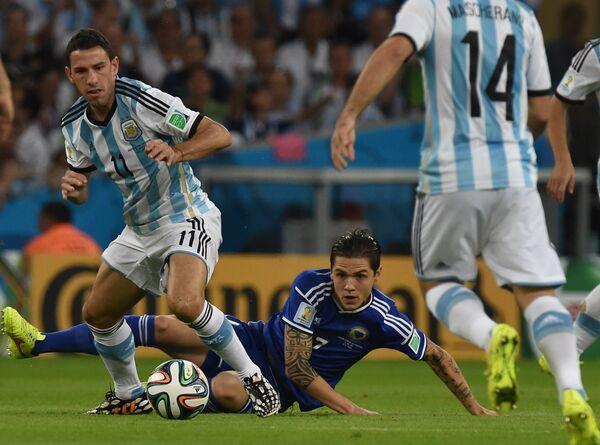 полузащитник сборной Аргентины Макси Родригес (слева) и защитник сборной Боснии и Герцеговины Мухамед Бешич (в центре).