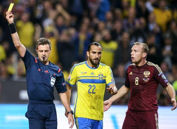 Главный судья матча показывает желтую карточку игроку сборной Швеции Эркау Зенгину (в центре)