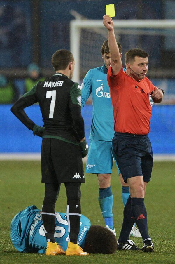 Главный судья Михаил Вилков (справа) показывает желтую карточку полузащитнику Краснодара Павлу Мамаеву (слева)